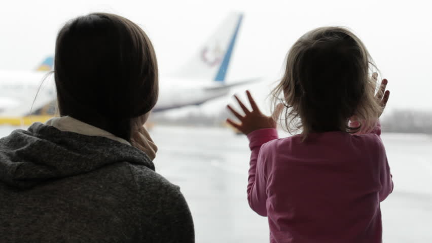 Close-up of attractive young mother and little daughter looking out the window at airport terminal, with airplane on the background. #22683028