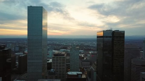 4k Aerial/drone footage of the skyscrapers of Denver, Colorado at sunset.  Rocky Mountains can be seen on the horizon