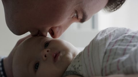 Close up slow motion shot of father caressing baby daughter / Provo, Utah, United States