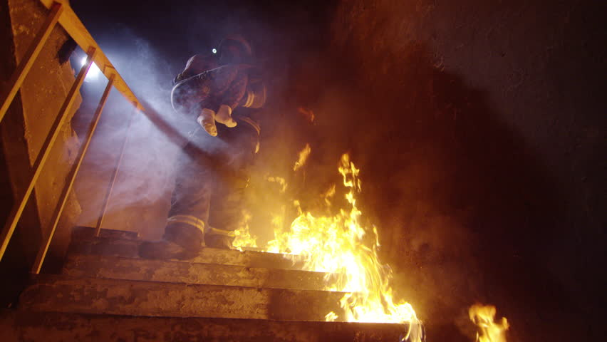 Brave Fireman Descends Burning Stairs with Saved Little Girl in His Hands. Open Flames are Seen Everywhere. Shot on RED Cinema Camera in 4K (UHD).