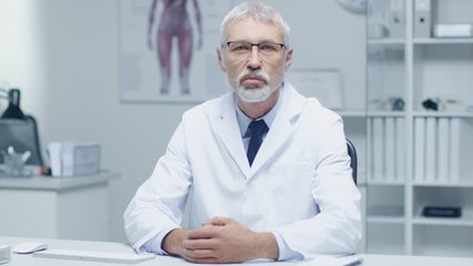 Experienced Gray Haired Senior Medical Practitioner Talking Into Camera. Portrait Shot in Modern and Light Office. Shot on RED Cinema Camera in 4K (UHD).
