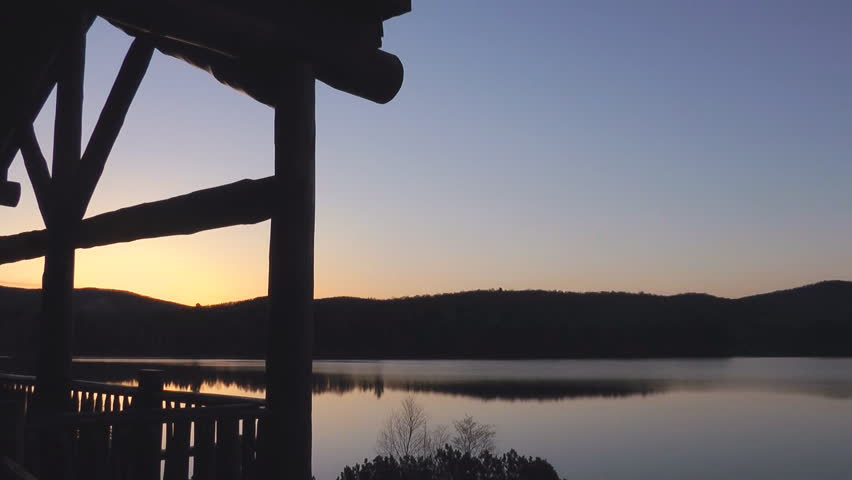 Time Lapse Of A Morning Sunrise Over A Lake In Quebec Canada With A Log Cabin Detail In The Foreground