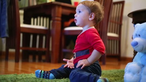 Little boy watching television in home, when his mother works laptop