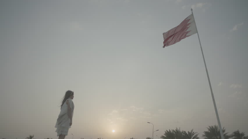 Bahrain Flag. Low-angle view at sunset of a Bahraini flag high up on a pole billowing in the breeze. A young woman walks towards the flagpole.