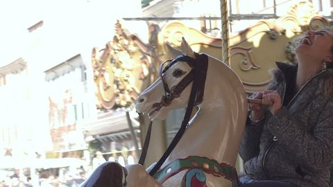 Happy woman has fun on the carousel- slow motion.