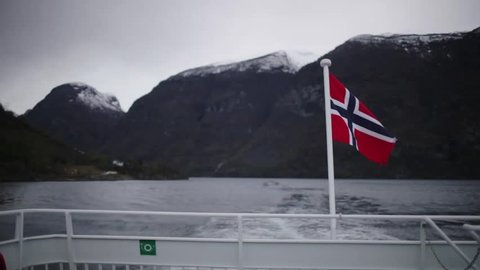 The Fjords, Norway. A Norwegian flag at the stern of the boat.
