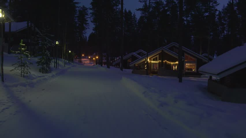 Moving at winter night by cozy wooden house in snowy forest village situated on lake shore in Finland .