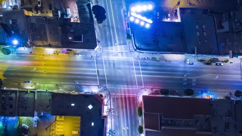 Vertical top down aerial view of traffic on street intersection at night. 4K UHD timelapse.