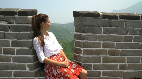 Great Wall China travel. Tourist woman in Asia relaxing sitting on famous Chinese tourist destination and attraction in Badaling north of Beijing.