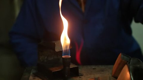 Shoemaker making shoes. Working with fire at cobbler workshop. Slow motion. Close up view.