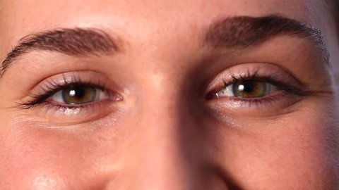 closeup of two cheerful young woman's eyes with contact lenses smiling, expressing herself, raising eyebrows for natural effect