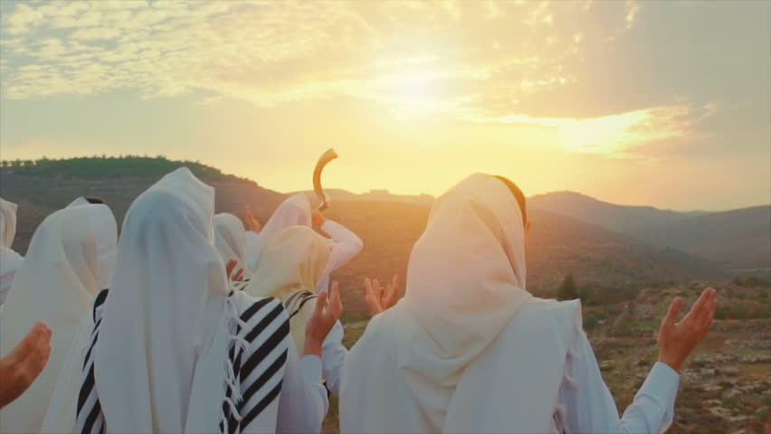 Jewish men pray With Talit and shofar in sunset