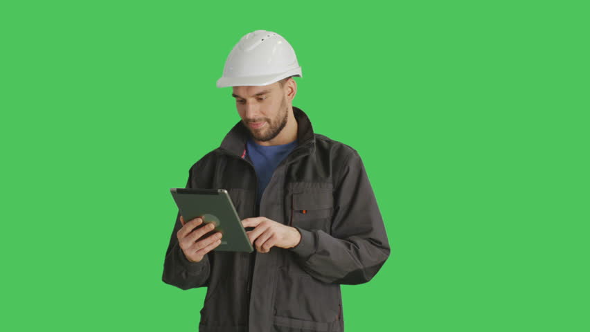 Mid Shot of a Handsome Worker Wearing White Hard Hat Using Tablet Computer Making Swiping Gestures on it. Shot on Green Screen Background. Shot on RED Cinema Camera 4K (UHD). | Shutterstock HD Video #22949881