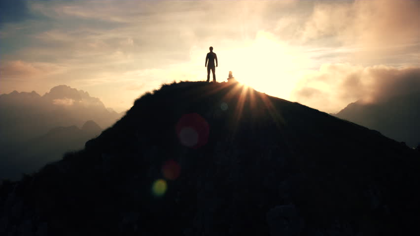 Aerial, edited - Moving above silhouette of a man standing on top of the mountain. Man raising arms victoriously after climbing the mountain | Shutterstock HD Video #22952884