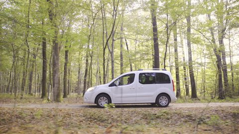 White minivan car driving slow through forest on gravel road side shot 4K. Wide shot on gimbal stabilizer moving at side of vehicle in focus while driving on middle of frame. Passing by trees.