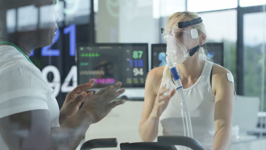 4K Female athlete on exercise bike being tested & monitored by sports scientist Dec 2016-UK | Shutterstock HD Video #22984798