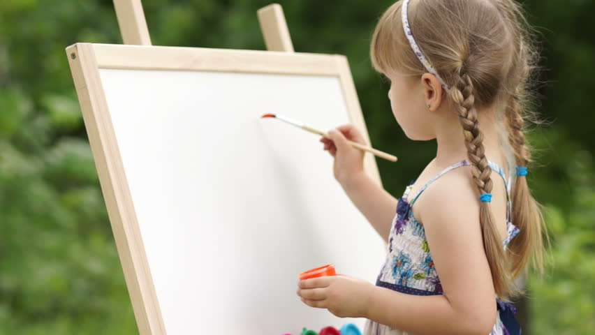 Little girl makes the first brush stroke on a painting