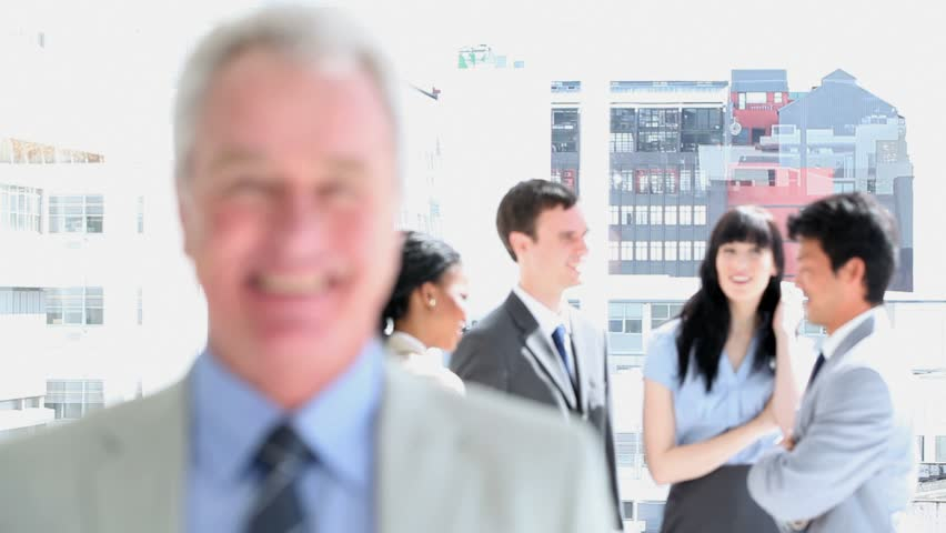 Smiling manager standing in front of his team in a bright room | Shutterstock HD Video #2301770