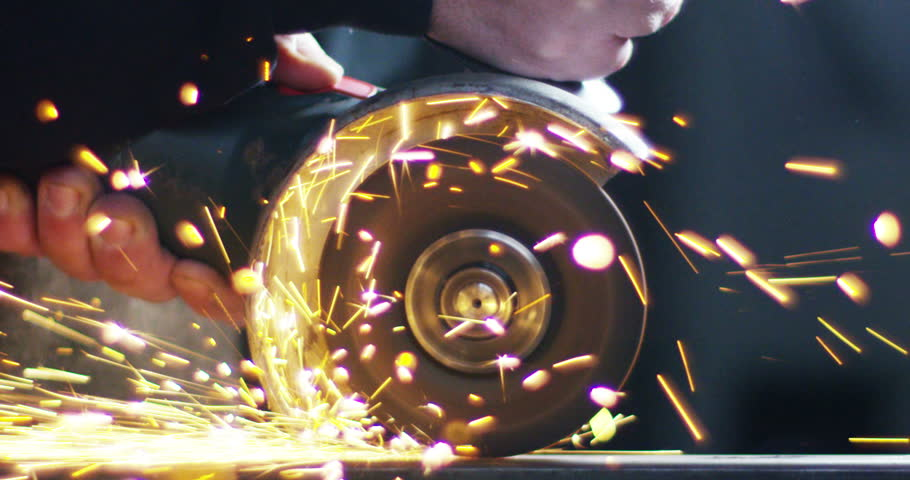 .blacksmith or welder,with its grinding smooths steel and iron,in extreme slow motion,to make the surface smooth.The grinding wheel contact with the iron causes sparks.concept:work,locksmith industry. #23023888