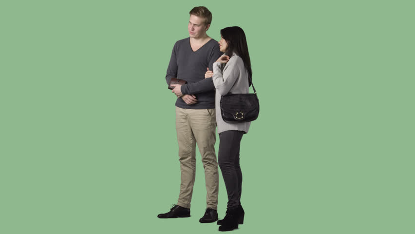 The couple is standing, discussing, looking at something. Green screen clip with alpha channel
