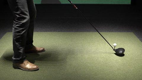 man drives golf ball into simulator