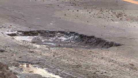 Pothole on city street causing damage to car tires if traffic passes over it.