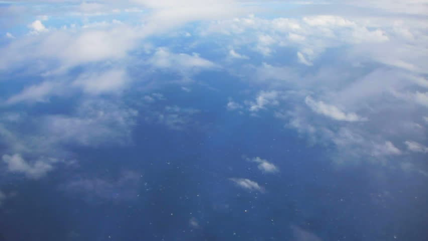 Flying in airplane over Pacific ocean dropping in altitude flying through clouds and little turbulence. | Shutterstock HD Video #2304410