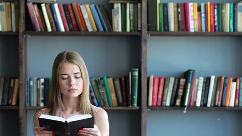 Cute teen girl learn close up. Smart 20s blonde model read a literature turning pages of the book holding hands closeup. Shelves with books on background and inspiration. Natural lighting indoors