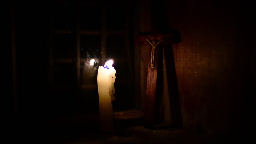A candle burns on the window. Outside night. The cross with a crucifix standing behind. Candle flame flickers and dies. Wooden windows frame in a wooden house in the mountains.