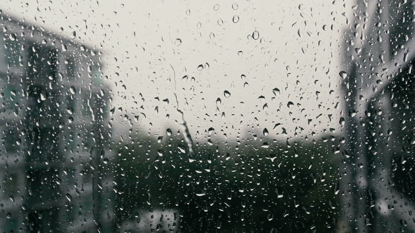 Drops of rain on a window pane, buildings in background. #23097298