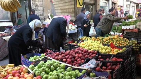 AMMAN, JORDAN - NOVEMBER 2016: People do grocery shopping at a popular fruit and vegetable market in downtown Amman, Jordan
