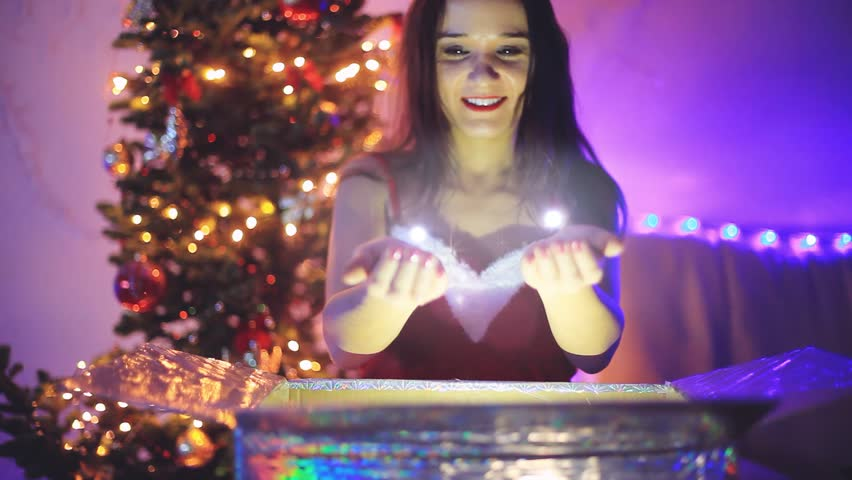 Young happy woman opening the magical Christmas present holds the shine lights. Girl sits next to Xmas tree at decorated home. 1920x1080