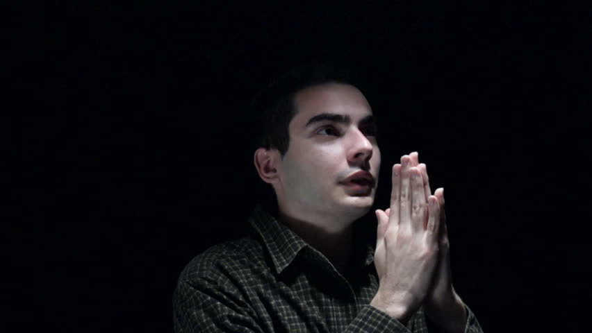 Christian young man praying in the dark.