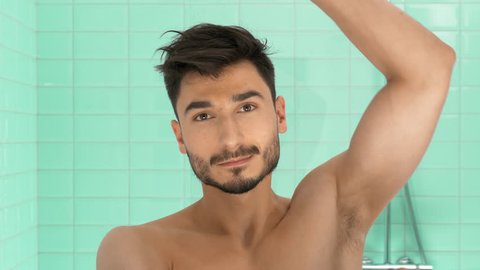 Handsome man applying deodorant on his armpit in bathroom