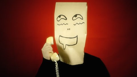 A creepy drooling excited breadbag face using a vintage rotary phone. Close-up shot, red background.