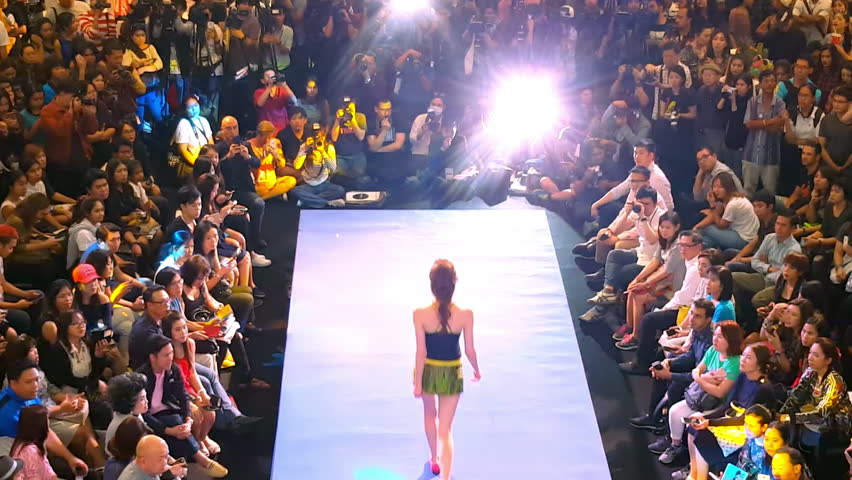 BANGKOK, THAILAND - 3 MAR 2016: attractive female model walks runway demonstrating beachwear to public and photographers at fashion show in shopping mall Siam Paragon. Back view. Footage with audio.