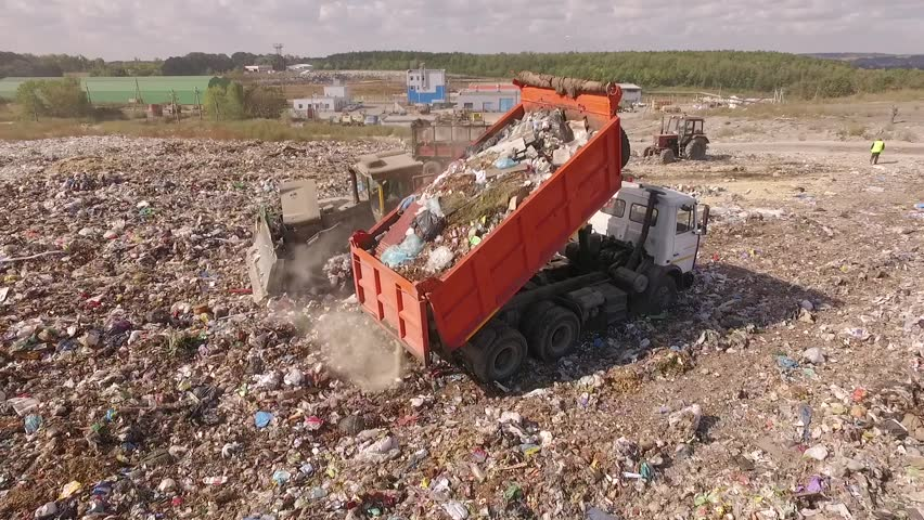 Aerial. Garbage truck and bulldozer on garbage dump.