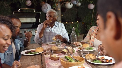 Adult black family eating outside at a dinner table