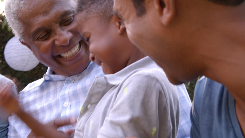 Young black boy playing with dad, uncle and grandad outdoors #23190118