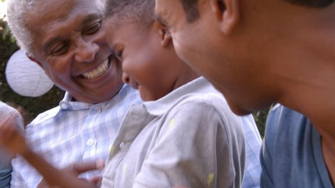 Young black boy playing with dad, uncle and grandad outdoors