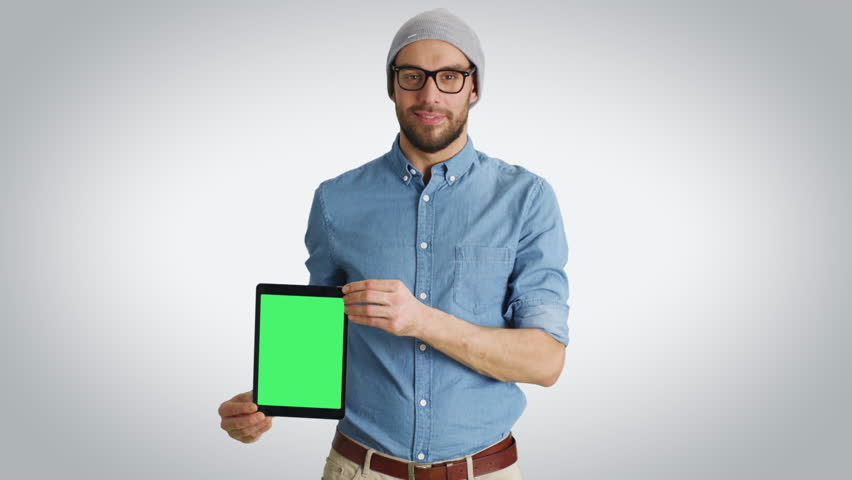 Mid Shot of a Fashionable Young Man in a Hat and Glasses Presenting to Us Tablet Computer with Isolated Green Screen. Shot on a White Background. Shot on RED Cinema Camera in 4K (UHD). | Shutterstock HD Video #23190583