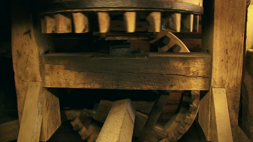 Cogwheels rotate in a 90-degree angle in an industrial corn mill. Sound of creaking and groaning of the timber