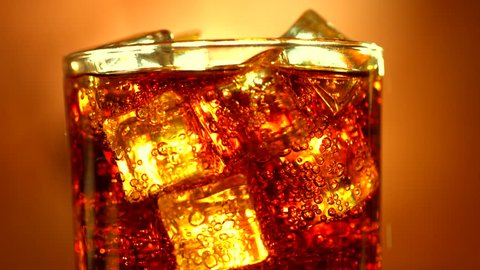 Cola pouring in glass with ice cubes over red background. Cola with Ice and bubbles in glass. Soda closeup. Food background. Close-up. 4K UHD video footage. Ultra high definition 3840X2160