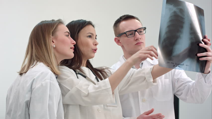 Three young doctors looking at spine x-ray | Shutterstock HD Video #23276614
