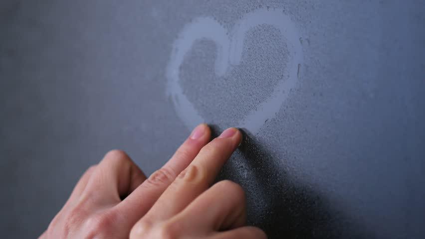 Woman's hand draws a heart on the frozen glass   Shutterstock HD Video #23329558