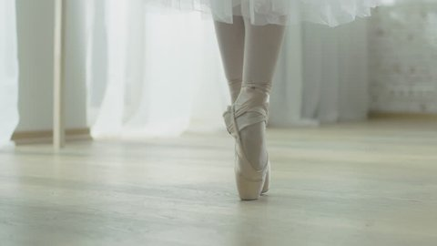 Close-up Shot of Ballerina's Legs. She Dances on Her Pointe Ballet Shoes. She's Wearing White Tutu Dress. Shot in a Bright and Sunny Studio. In Slow Motion.Shot on RED EPIC-W 8K Helium Cinema Camera.