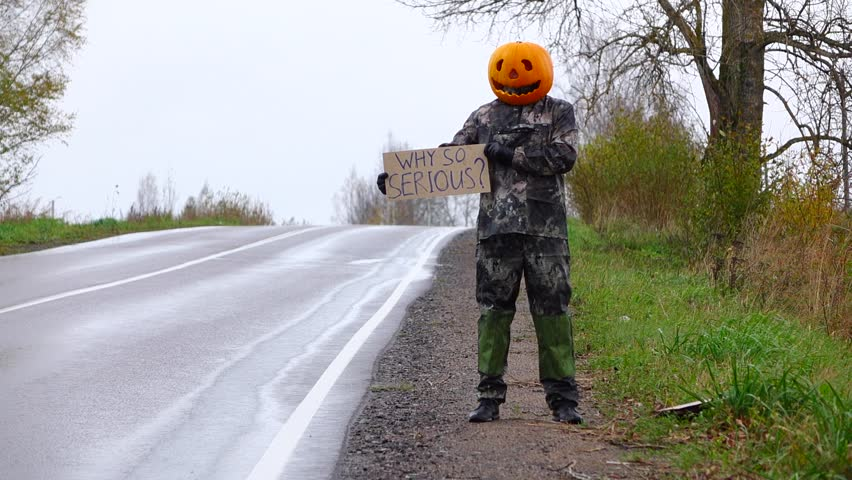 Joky man with bright orange carved pumpkin on his head stand with written sign on roadside, hitching parody, ask why so serious. No cars on rural road, guy put down carton plate. Rainy country area