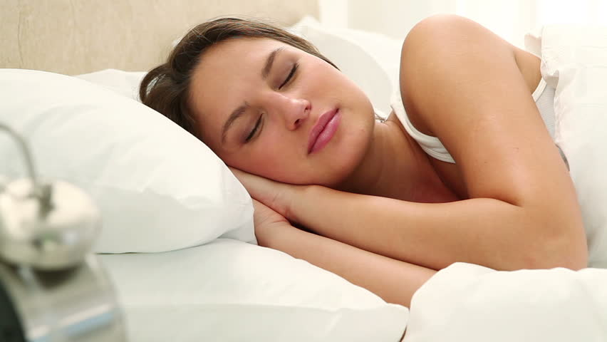 Woman going back to sleep while lying in her bed