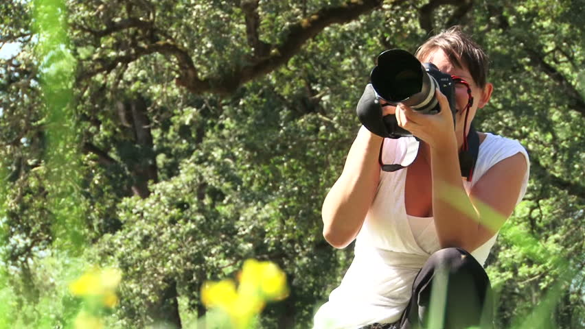 Woman photographer takes pictures outdoors.