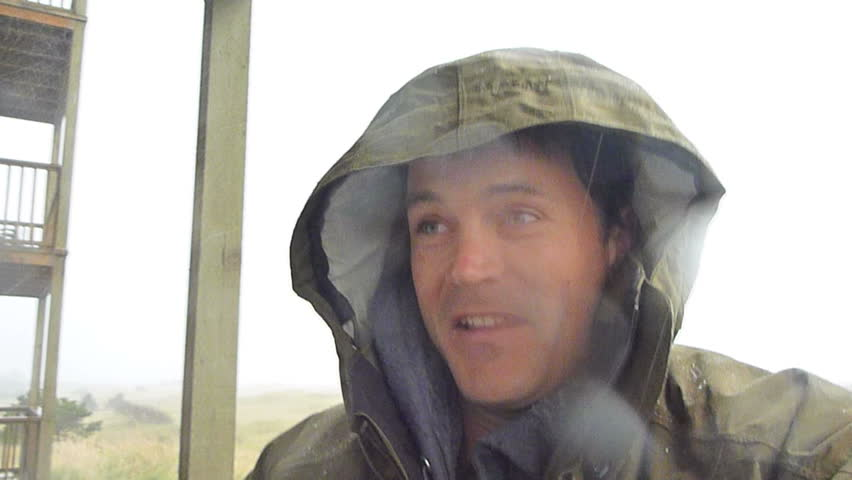 Man standing outside gets rained on and blown by heavy winds during rain storm.